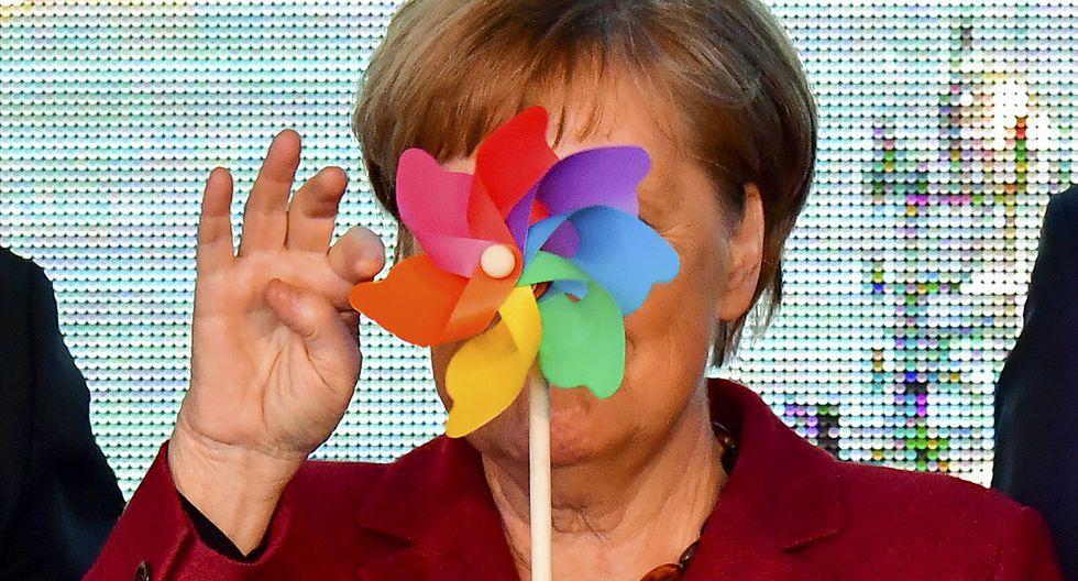 La canciller alemana Angela Merkel está oculta en parte por una rueda de viento de juguete mientras posa con los niños durante la ceremonia de inauguración del parque eólico Arkona en Sassnitz, norte de Alemania, el 16 de abril de 2019.  (TOBIAS SCHWARZ / AFP)
