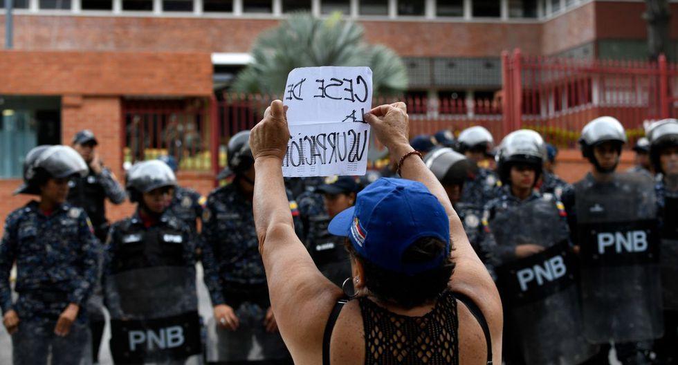 Vigilado por policías antimotines, un pequeño grupo leyó el pregón frente a la comandancia de la Armada en el centro de Caracas, sin incidentes. (Foto: AFP)