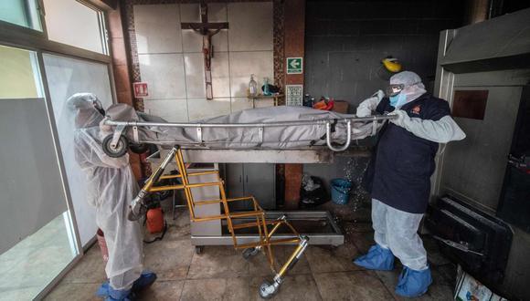 Trabajadores de la morgue mueven el cuerpo de una víctima de COVID-19 en un crematorio en Cuautitlan Izcalli, México. (AFP/PEDRO PARDO).