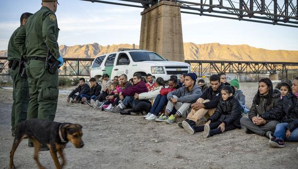 En esta foto de archivo, un grupo de unos 30 migrantes brasileños, que acababan de cruzar la frontera, se sientan en el suelo cerca de los agentes de la Patrulla Fronteriza de Estados Unidos. (Foto referencial: Paul Ratje / AFP).