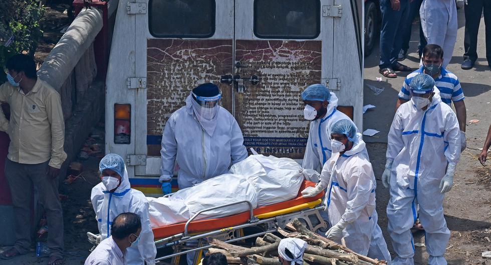 Personal sanitario lleva un cadáver al lugar de cremación. (Foto: AFP)