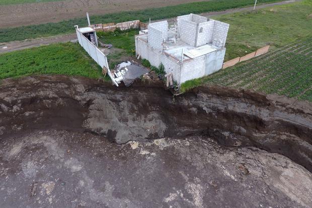MEX3537. JUAN C. BONILLA (MÉXICO), 04/06/2021.- Fotografía tomada desde un drone que muestra el socavón de 97 metros de diámetro y una profundidad aproximada de 20 metros hoy, en el municipio de Juan C. Bonilla, en el estado de Puebla (México). El gran socavón aparecido hace casi una semana en el céntrico estado mexicano de Puebla siguió extendiéndose este viernes y provocó el derrumbe de una barda y de una recámara de la casa ubicada en el borde del agujero. EFE/ Hilda Ríos