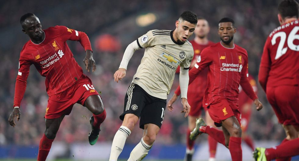 Manchester United's Belgian-born Brazilian midfielder Andreas Pereira (C) is challenged by Liverpool's Senegalese striker Sadio Mane (L) during the English Premier League football match between Liverpool and Manchester United at Anfield stadium in Liverpool, north west England on January 19, 2020.  - RESTRICTED TO EDITORIAL USE. No use with unauthorized audio, video, data, fixture lists, club/league logos or 'live' services. Online in-match use limited to 120 images. An additional 40 images may be used in extra time. No video emulation. Social media in-match use limited to 120 images. An additional 40 images may be used in extra time. No use in betting publications, games or single club/league/player publications.  / AFP / Paul ELLIS / RESTRICTED TO EDITORIAL USE. No use with unauthorized audio, video, data, fixture lists, club/league logos or 'live' services. Online in-match use limited to 120 images. An additional 40 images may be used in extra time. No video emulation. Social media in-match use limited to 120 images. An additional 40 images may be used in extra time. No use in betting publications, games or single club/league/player publications.