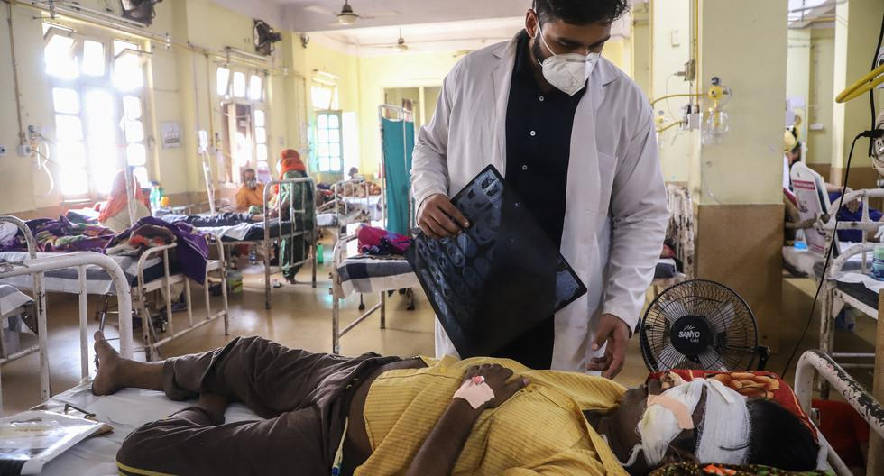 """Un médico asiste a un paciente con coronavirus que padece del """"hongo negro"""", una infección fúngica rara y mortal, mientras recibe tratamientos en el hospital NSCB en Jabalpur, el 20 de mayo de 2021 (Foto:  Uma Shankar MISHRA / AFP)."""