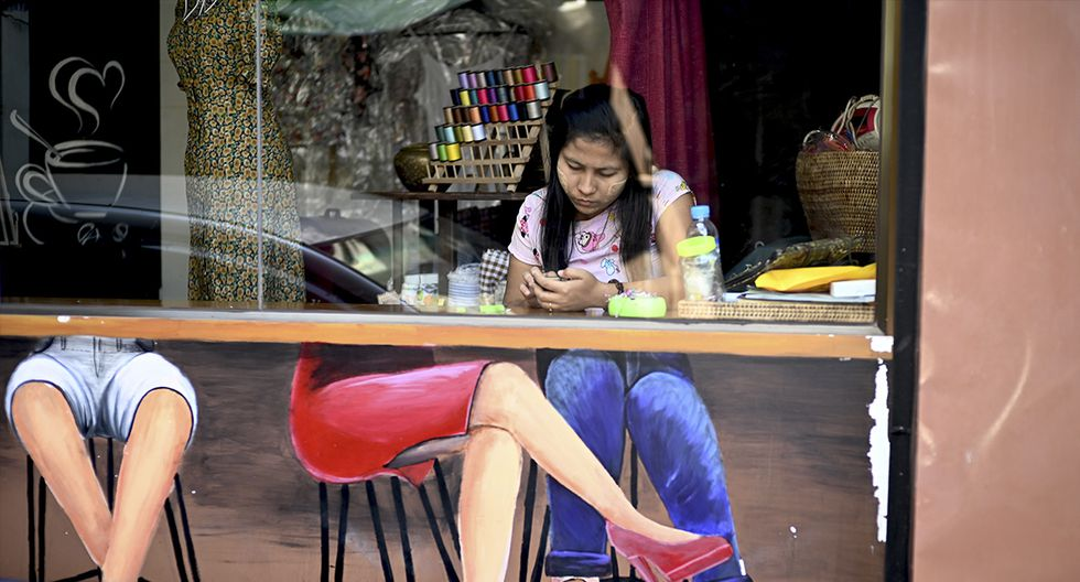 Una mujer usa un teléfono móvil mientras espera clientes en su tienda de telas en un mercado en Yangon el 21 de febrero de 2019. (JOYA SAMAD / AFP)