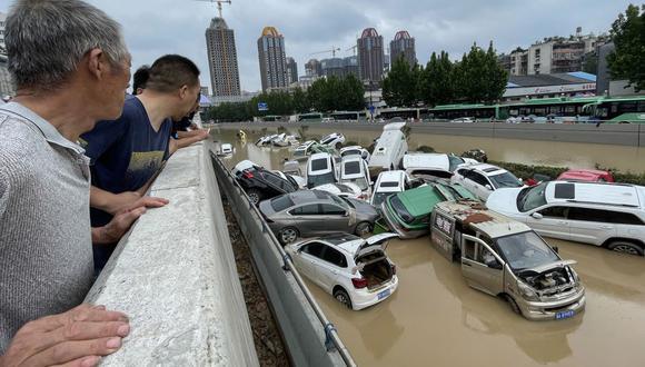 La gente mira los automóviles que se arrastrados por las inundaciones en Zhengzhou. (Foto de STR / AFP).