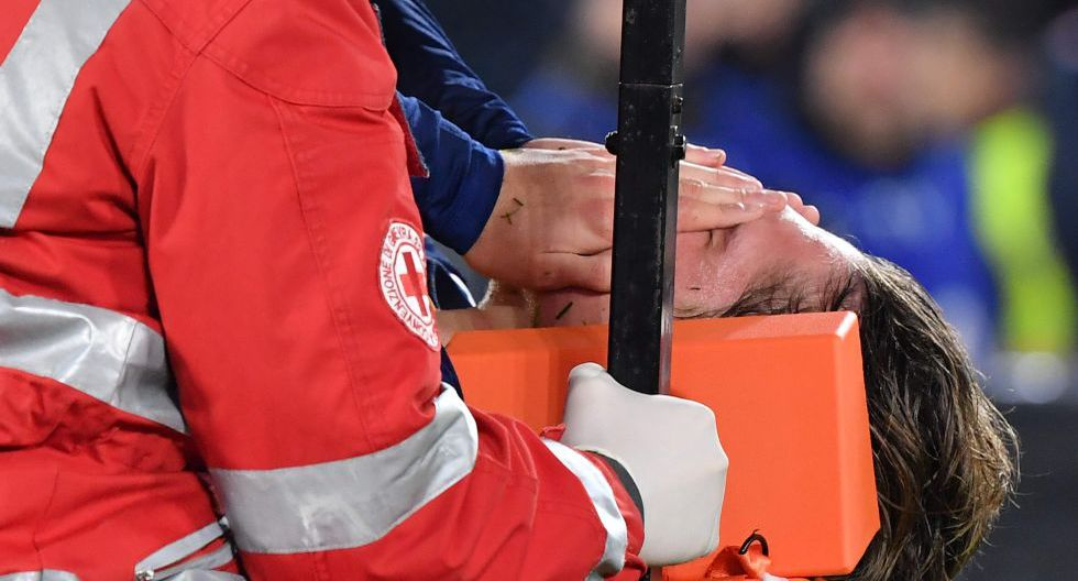 AS Roma's Italian midfielder Nicolo Zaniolo holds his face in pain as he is stretched out of the pitch after being injured during the Italian Serie A football match AS Roma vs Juventus on January 12, 2020 at the Olympic stadium in Rome. / AFP / Andreas SOLARO