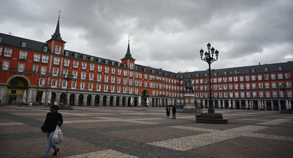 Una mujer es vista llevando bolsas de supermercado por la Plaza Mayor en el centro de Madrid el 27 de marzo de 2020. Los españoles inician este sábado su tercer fin de semana de confinamiento por la pandemia de COVID-19, que se prolongará al menos hasta el 11 de abril. (AFP).