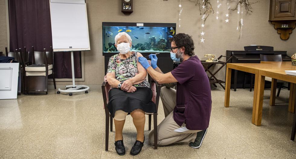 Una mujer mayor de 90 años recibe su primera dosis de la vacuna Pfizer-BioNTech COVID-19. Se trata de la primera persona en el país en recibir el pinchazo, en un domicilio en Lucerna, Suiza, el 23 de diciembre de 2020. (EFE/EPA/URS FLUEELER).