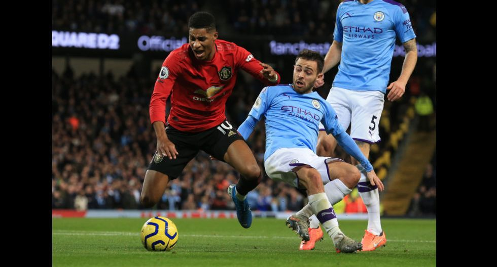 Manchester United's English striker Marcus Rashford (L) goes down fouled by Manchester City's Portuguese midfielder Bernardo Silva (R) to win a penalty leading to the first goal during the English Premier League football match between Manchester City and Manchester United at the Etihad Stadium in Manchester, north west England, on December 7, 2019. (Photo by Lindsey Parnaby / AFP) / RESTRICTED TO EDITORIAL USE. No use with unauthorized audio, video, data, fixture lists, club/league logos or 'live' services. Online in-match use limited to 120 images. An additional 40 images may be used in extra time. No video emulation. Social media in-match use limited to 120 images. An additional 40 images may be used in extra time. No use in betting publications, games or single club/league/player publications. /