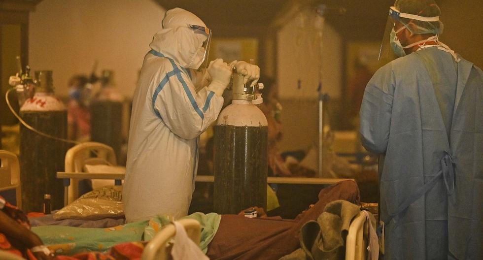 Los trabajadores de la salud que usan equipo de protección personal (equipo de protección personal) atienden a pacientes positivos para el coronavirus en un centro de atención en Nueva Delhi (India), el 28 de abril de 2021. (Prakash SINGH / AFP).