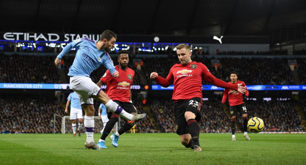 Manchester City's Portuguese midfielder Bernardo Silva (L) crosses the ball past Manchester United's English defender Luke Shaw (R) during the English Premier League football match between Manchester City and Manchester United at the Etihad Stadium in Manchester, north west England, on December 7, 2019. (Photo by Oli SCARFF / AFP) / RESTRICTED TO EDITORIAL USE. No use with unauthorized audio, video, data, fixture lists, club/league logos or 'live' services. Online in-match use limited to 120 images. An additional 40 images may be used in extra time. No video emulation. Social media in-match use limited to 120 images. An additional 40 images may be used in extra time. No use in betting publications, games or single club/league/player publications. /