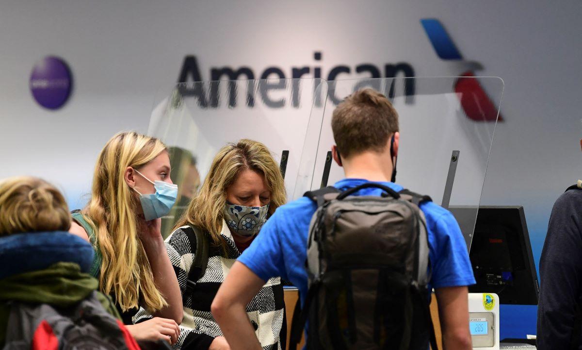 Viajeros en el mostrador de check-in de American Airlines en el Aeropuerto Internacional de Los Ángeles, Estados Unidos, el 1 de octubre de 2020, en medio de la pandemia de coronavirus (Foto: Frederic J. BROWN / AFP).