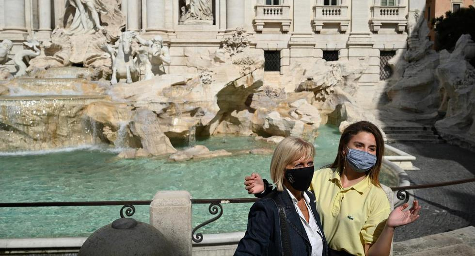 Tourists wearing a face pose by the Trevi Fountain in downtown Rome on September 25, 2020 during the COVID-19 pandemic, caused by the novel coronavirus. - Italy, which was hit hard by the first wave of the coronavirus, is today an exception in Europe with a limited number of new cases, a result obtained at the price of strict anti-COVID measures, hailed on September 25, 2020 by the World Health Organization (WHO). (Photo by Vincenzo PINTO / AFP)
