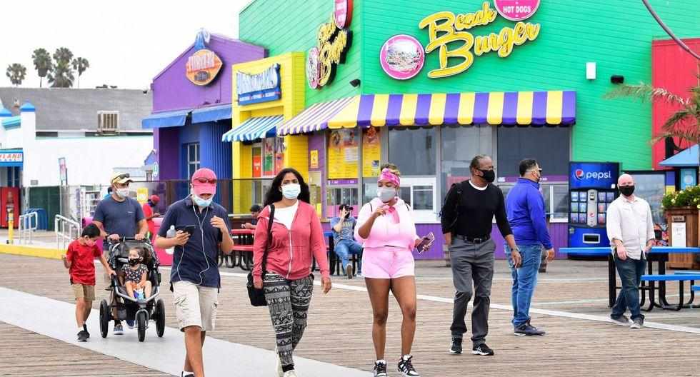 Las personas que usan máscaras faciales visitan el muelle de Santa Mónica, que volvió a abrir el 25 de junio después del cierre durante más de tres meses debido a la pandemia de coronavirus. (AFP / Frederic J. BROWN)