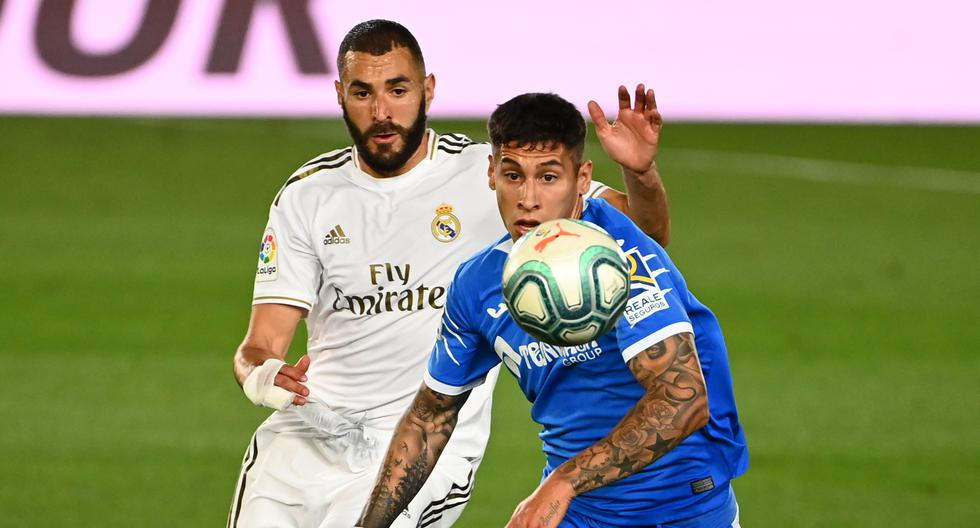 Real Madrid's French forward Karim Benzema (L) challenges Getafe's Uruguayan defender Mathias Olivera during the Spanish league football match Real Madrid CF against Getafe CF at the Alfredo di Stefano stadium in Valdebebas, on the outskirts of Madrid, on July 2, 2020. / AFP / GABRIEL BOUYS