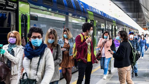 Los pasajeros llegan de los trenes regionales a la estación de tren de Cardona en Milán (Photo by Miguel MEDINA/AFP).
