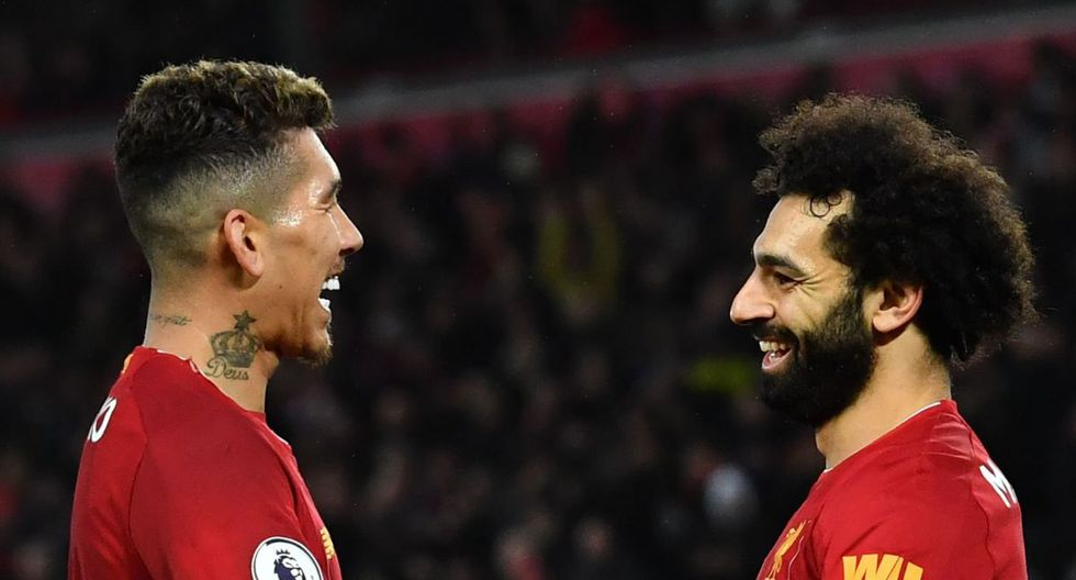 Liverpool's Egyptian midfielder Mohamed Salah (R) celebrates with Liverpool's Brazilian midfielder Roberto Firmino after scoring his team's fourth goal during the English Premier League football match between Liverpool and Southampton at Anfield in Liverpool, north west England on February 1, 2020.  - RESTRICTED TO EDITORIAL USE. No use with unauthorized audio, video, data, fixture lists, club/league logos or 'live' services. Online in-match use limited to 120 images. An additional 40 images may be used in extra time. No video emulation. Social media in-match use limited to 120 images. An additional 40 images may be used in extra time. No use in betting publications, games or single club/league/player publications.  / AFP / Paul ELLIS / RESTRICTED TO EDITORIAL USE. No use with unauthorized audio, video, data, fixture lists, club/league logos or 'live' services. Online in-match use limited to 120 images. An additional 40 images may be used in extra time. No video emulation. Social media in-match use limited to 120 images. An additional 40 images may be used in extra time. No use in betting publications, games or single club/league/player publications.