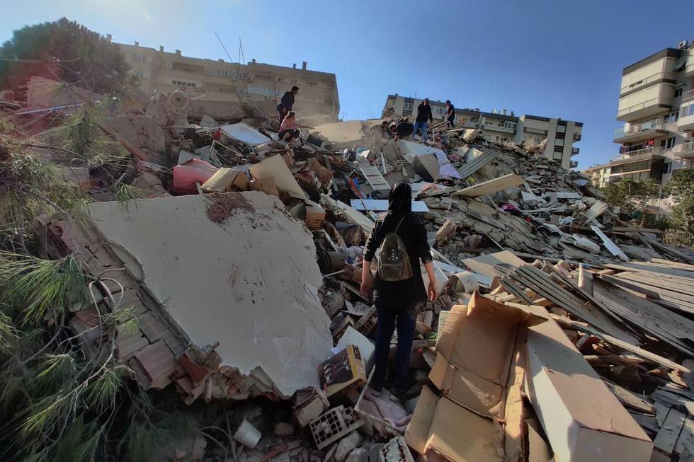 Personas son vistas en un edificio derrumbado tras un terremoto de magnitud 7,0 en el mar Egeo en Esmirna, Turquía. (EFE/EPA/Mehmet Emin Menguarslan).