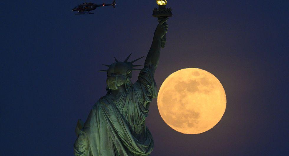 Un helicóptero pasa volando cuando la luna llena se eleva detrás de la Estatua de la Libertad el 18 de mayo de 2019 en la ciudad de Nueva York. (JOHANNES EISELE / AFP)