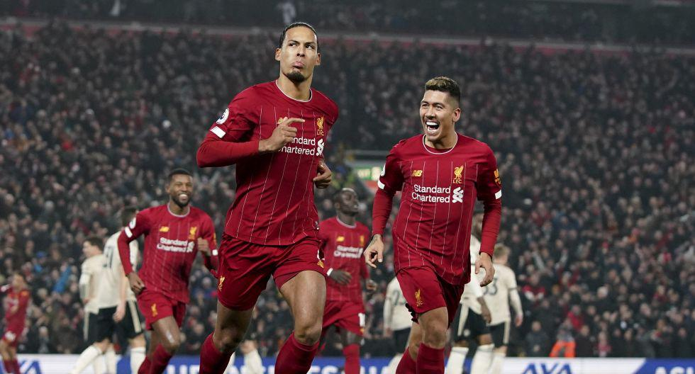 Liverpool's Virgil van Dijk, left, celebrates scoring his side's first goal during the English Premier League soccer match between Liverpool and Manchester United at Anfield Stadium in Liverpool, Sunday, Jan. 19, 2020.(AP Photo/Jon Super)