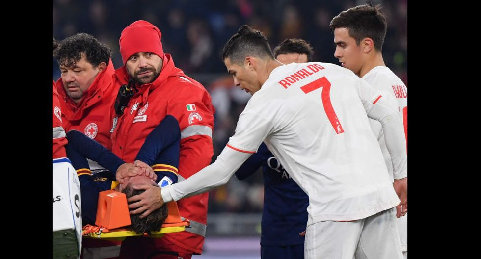 Juventus' Portuguese forward Cristiano Ronaldo (r) tends to AS Roma's Italian midfielder Nicolo Zaniolo as he is stretched out of the pitch after being injured during the Italian Serie A football match AS Roma vs Juventus on January 12, 2020 at the Olympic stadium in Rome. / AFP / Andreas SOLARO