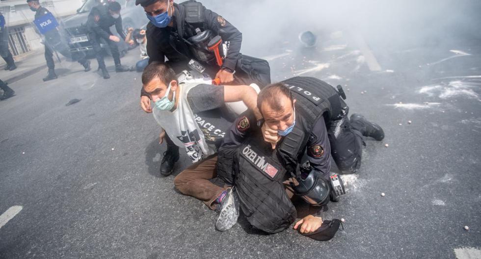 La policía turca detiene a una persona mientras se enfrentan durante una manifestación del Primero de Mayo que marca el día internacional del trabajador en Estambul, el 1 de mayo de 2021. (BULENT KILIC / AFP).