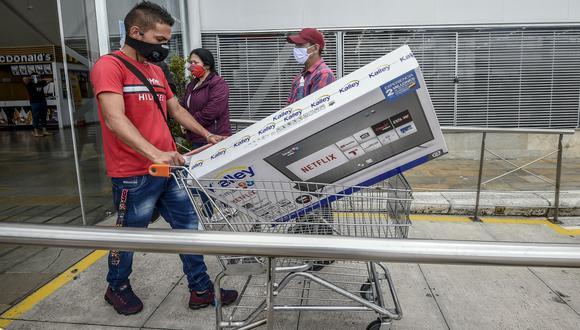 Un hombre empuja un carrito con un televisor. (Foto por Juan BARRETO / AFP).