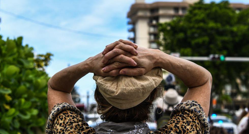 Una persona reacciona mientras observa a los rescatistas que buscan entre los escombros en el sitio de un edificio derrumbado en Surfside, Florida, al norte de Miami Beach (Estados Unidos), el 26 de junio de 2021. (CHANDAN KHANNA / AFP).