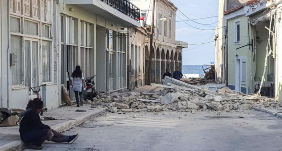 La gente pasa frente a una casa destruida después del terremoto en la isla de Samos el 30 de octubre de 2020. (AFP / Eurokinissi / STR).