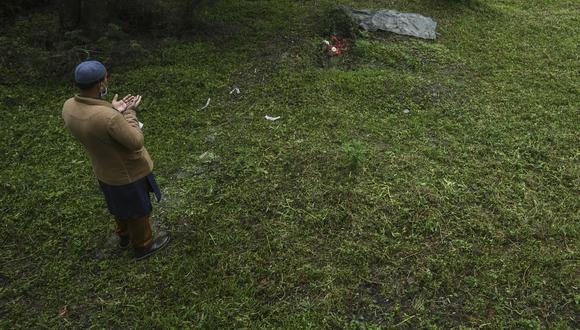 Imagen referencial de una persona rezando frente a una tumba, el 21 de julio de 2021. (PRAKASH MATHEMA / AFP).