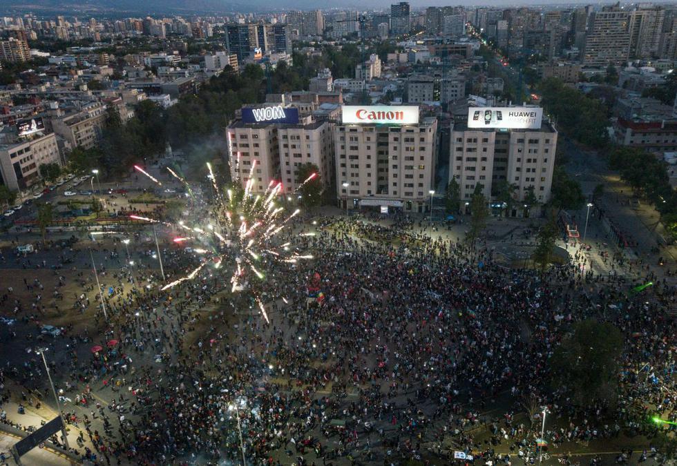 Vista aérea que muestra a manifestantes apoyando la reforma de la constitución chilena esperando los resultados oficiales del referéndum en la plaza Italia en Santiago. (AFP/ JAVIER TORRES).