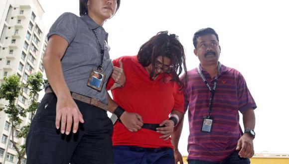 Esta foto proporcionada por The Straits Times, tomada el 3 de agosto de 2016, muestra a agentes de policía escoltando a Gaiyathiri Murugayan a su casa para investigar el asesinato de su empleada doméstica. (Foto: AFP).