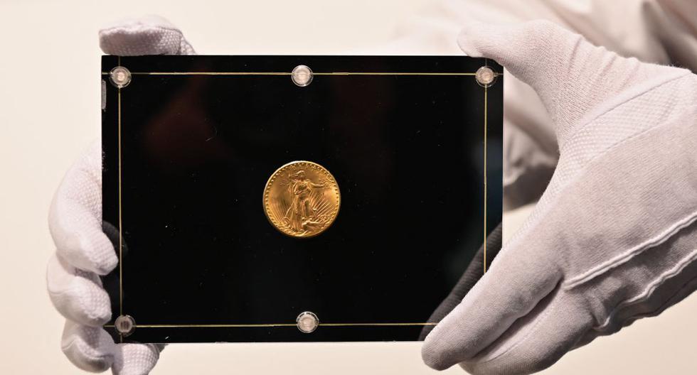 En esta foto de archivo tomada el 11 de marzo de 2021, un empleado de Sotheby's sostiene una moneda Double Eagle de 1933. (Angela Weiss / AFP).