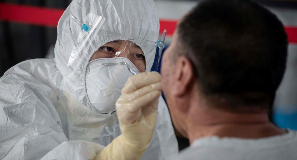 Imagen referencial. Un trabajador de la salud realiza una prueba de hisopo a un hombre en un área al aire libre en Beijing (China). (AFP / NICOLAS ASFOURI).