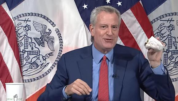 El alcalde de Nueva York, Bill de Blasio, presentó la promoción comiéndose una hamburguesa de la popular cadena de comida rápida Shake Shack en plena conferencia de prensa. (Foto: captura YouTube)