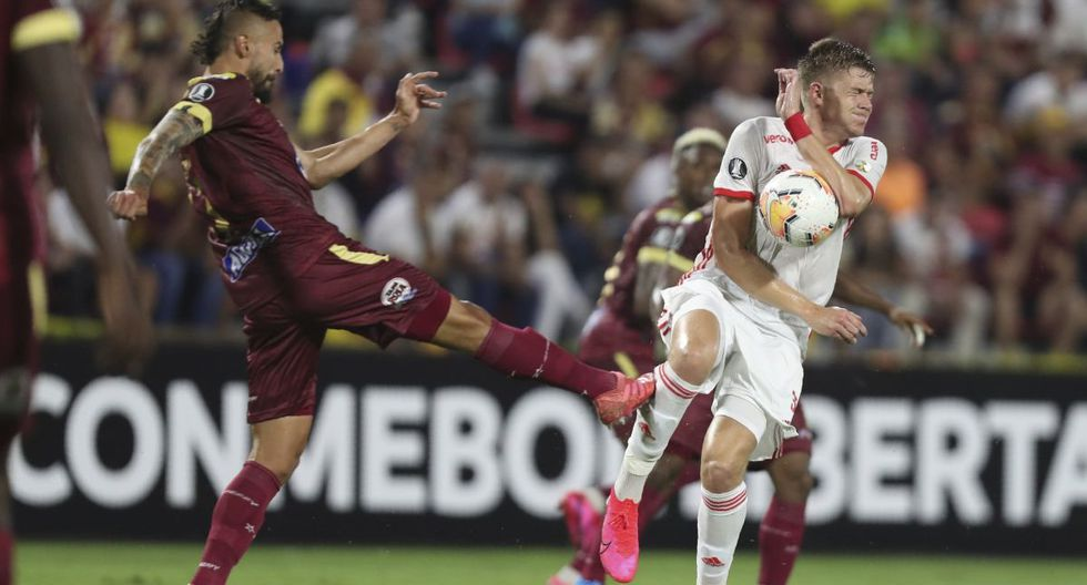 Jose David Moya of Colombia's Deportes Tolima, left, fights for the ball with Bruno of Brazil's Internacional during a Copa Libertadores soccer match at the Manuel Murillo Toro stadium in Ibague, Colombia, Wednesday, Feb., 19, 2020. (AP Photo/Fernando Vergara)