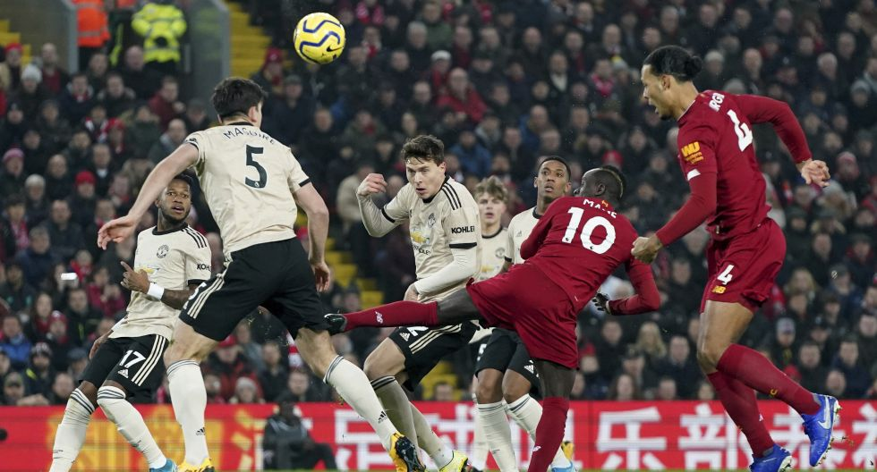 Liverpool's Sadio Mane, centre, kicks the ball during the English Premier League soccer match between Liverpool and Manchester United at Anfield Stadium in Liverpool, Sunday, Jan. 19, 2020.(AP Photo/Jon Super)