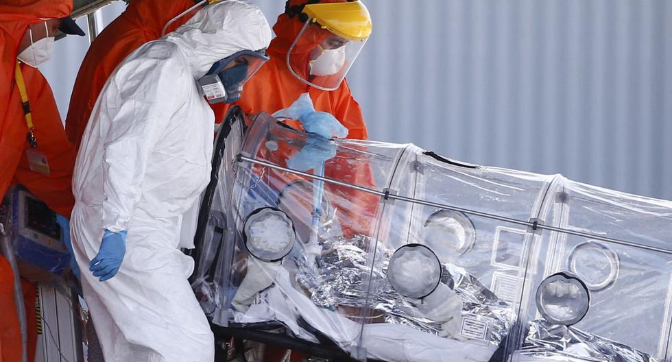 El personal médico atiende a un paciente infectado con la enfermedad del coronavirus a su llegada en avión desde Osorno el 25 de enero de 2021 a un aeropuerto militar de Santiago de Chile.  (JAVIER TORRES / AFP).