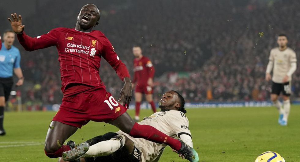 Liverpool's Sadio Mane, left, and Manchester United's Aaron Wan-Bissaka challenge for the ball during the English Premier League soccer match between Liverpool and Manchester United at Anfield Stadium in Liverpool, Sunday, Jan. 19, 2020.(AP Photo/Jon Super)