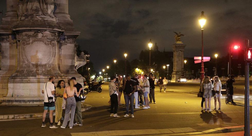 La gente se para en una calle cerca de Les Invalides en París después del toque de queda por el coronavirus. (GEOFFROY VAN DER HASSELT / AFP).