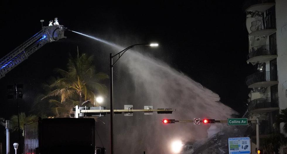 Un equipo de bomberos de Miami-Dade rocía agua sobre los escombros mientras continúan los esfuerzos de rescate donde un ala de un edificio de condominios frente a la playa de 12 pisos se derrumbó, el jueves 24 de junio de 2021 en el área de Surfside de Miami. (AP/Gerald Herbert).