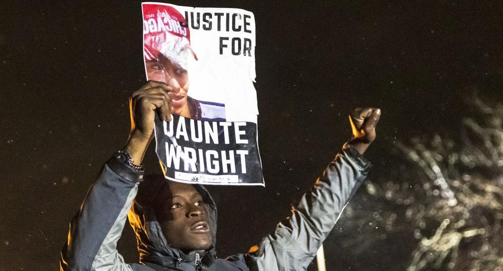 """Un manifestante sostiene una foto de Daunte Wright y grita """"No disparen"""" a la policía después del toque de queda mientras protestaban por la muerte de Daunte Wright, en Brooklyn Center, Minnesota, el 13 de abril de 2021. (Kerem YUCEL / AFP)."""