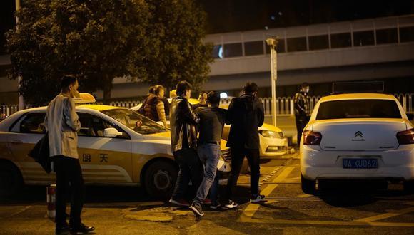 Un hombre es ayudado por amigos a subirse a un taxi frente a una discoteca. (Aly Song / Reuters).