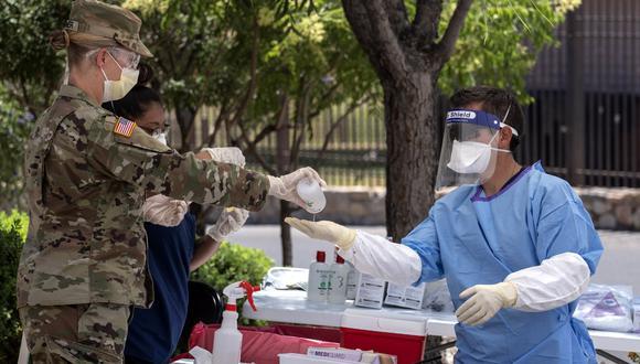 Un soldado de la Guardia Nacional de Texas recibe desinfectante de manos después de analizar a las personas para detectar COVID-19 en el estacionamiento de Memorial Swimming Pool, en El Paso, Texas. (Foto: AFP)