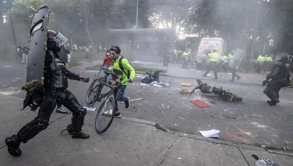 Manifestantes chocan con la policía antidisturbios en Bogotá durante una protesta por la muerte de un abogado bajo custodia policial. (Foto de Juan BARRETO / AFP).