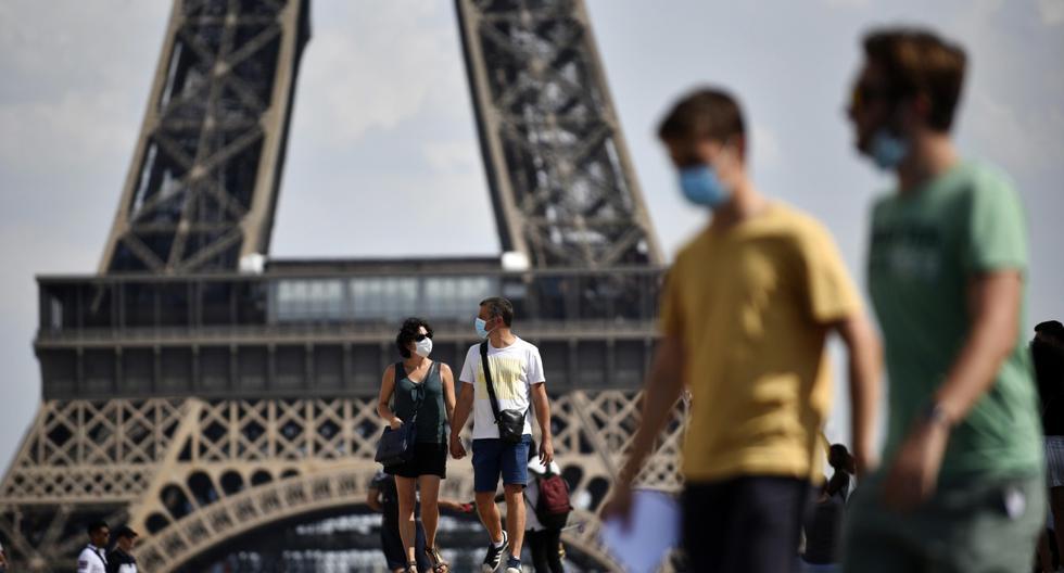 Personas con mascarillas caminan frente a la Torre Eiffel, como parte de las medidas para contener la propagación del coronavirus en París (Francia). (EFE/EPA/Julien de Rosa).