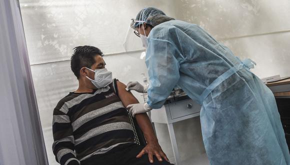 Un trabajador de salud prepara a un voluntario para recibir una vacuna COVID-19 producida por el chino Sinopharm durante su ensayo en el Centro de Estudios Clínicos de la Universidad Cayetano Heredia en Lima el 09 de diciembre de 2020. (Foto: AFP)