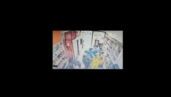 Momento del hurto. En la imagen se observa a uno de los ladrones recostado sobre el mostrador sacando el celular y el dinero. Delante, sus cómplices, uno de ellos de contextura gruesa, tapando la visión a la trabajadora. | Reproducción de vídeo