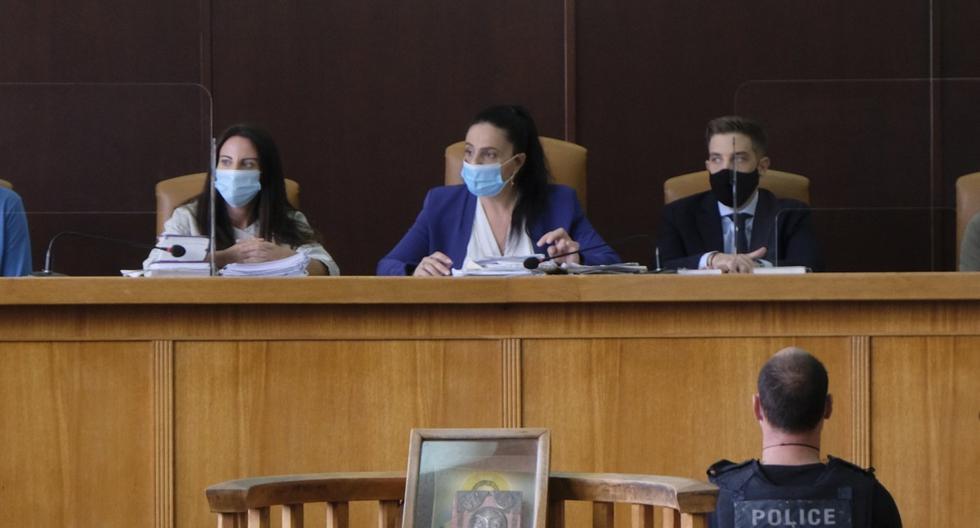 """Yiannis Paraskakis, abajo a la derecha y  con un chaleco antibalas que dice """"policía griega"""", se sienta en una sala de un tribunal en el primer día de su juicio en Rethymno, en la isla de Creta. (AP/Giannis Angelakis)."""